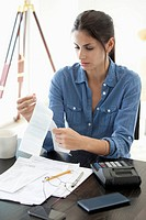 Woman at desk looking at receipts