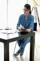 Woman using calculator at desk (thumbnail)