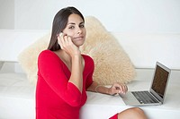 Woman in red on phone and with laptop (thumbnail)