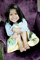 A young smiling girl sitting in a purple armchair