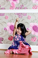 A young girl holding a swirl lollipop aloft