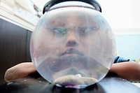 A frowning boy looking through a fishbowl with no fish