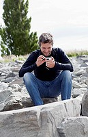 A man sitting on a rock, smiling at something on his smart phone