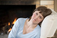 A serene young woman sitting near a roaring fire