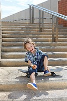 Boy sitting on skateboard on steps