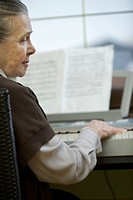 A senior woman sitting at piano