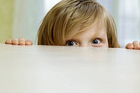 A mischievous girl peeking over the top of a table