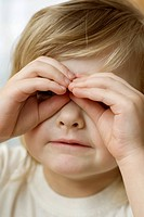 A little girl looking through glasses made from her fingers