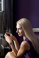 A beautiful young woman holding a glass of red wine