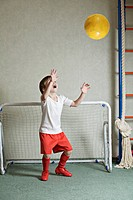 A young boy defending a goal while a ball flies towards him