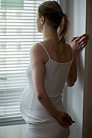 A pregnant woman standing looking out a window