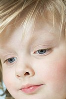 A cute little girl looking down, extreme close_up