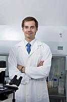 A smiling research technician standing in a research lab