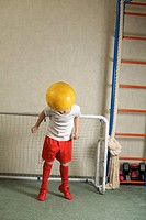 A young boy jumping to head butt a soccer ball away from a goal