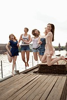 Five young female friends jumping in the air on a jetty next to the Spree, Berlin, Germany