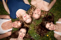 Five cheerful female friends lying in the grass, head and shoulders (thumbnail)