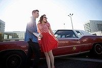 A cheerful rockabilly couple standing next to a vintage car