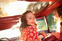 Two rockabilly women having fun in the front seat of a vintage car (thumbnail)