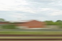 A landscape with buildings in blurred motion, viewed from moving train