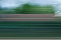 A building, trees and clouds in abstract blurred pattern viewed from moving train