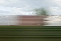 A building and sky in blurred abstract pattern seen from moving train