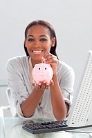 Smiling ethnic businesswoman saving money in a piggybank