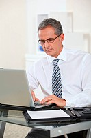 Portrait of businessman working on laptop computer