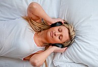 Bright woman listenning music on a bed