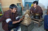 Bhutanesische Kunststudenten in Nationaltracht am Nationalinstitut für traditionelles Kunsthandwerk Zorig Chusum bei der Herstellung von traditionelle...