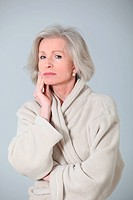 Senior woman in bathrobe standing on white background