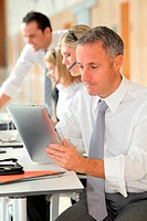 Office worker looking at internet on electronic pad