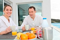 Couple having breakfast in their home terrace