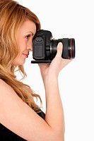 Lovely blond_haired woman taking a photo with a camera