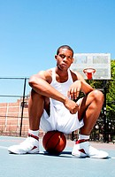 Basketball player sitting on ball