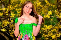 a girl stands near Forsythia bush