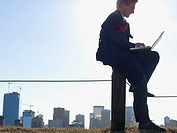Canada, Alberta, Calgary, Businessman working on laptop in park above city