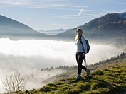 Italy, Piedmont, Woman looking at mountains from meadow above fog
