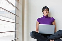 Portrait of businesswoman using laptop in office