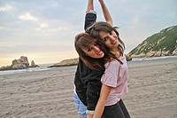 Two happy young women at El Sablón beach, Asturias, Spain