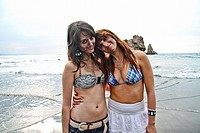 Two happy young women at El Sablón beach, Asturias, Spain.