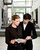Two women reading a magazine while standing in an office buildin