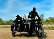 Two armed men riding a motorcycle with a sidecar. Motion blur.