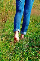A woman in blue jeans walking barefoot on the grass