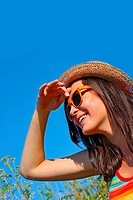 A smiling, pretty, young girl wearing a straw hat and orange sunglasses smiling and looking straight ahead