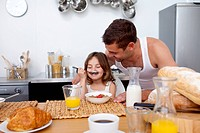 Little girl enjoying her breakfast with her father
