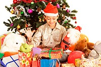 Portrait of a boy sitting with presents under Christmas tree