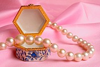 Partial view of a pearl necklace on a jewelery box
