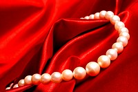 Partial view of a pearl necklace on a satin cloth