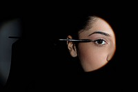 Young woman applying mascara to her lashes