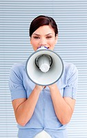 Positive businesswoman yelling through a megaphone